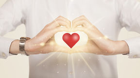 Händer som skapar en form med glänsande hjärta Arkivfoto