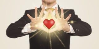 Händer som skapar en form med glänsande hjärta Arkivfoton