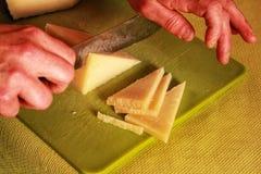 Händer som skivar Manchego ostskivor i trianglar arkivbilder