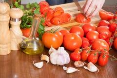 Händer som skivar tomater på tabellen Arkivfoto