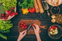 Händer som skivar tomater vid kniven Arkivbilder