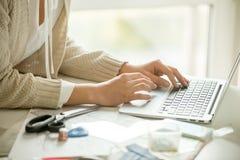 Händer som skrivar ut på en bärbar dator som omkring syr tillbehör Royaltyfri Foto