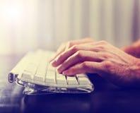 Händer som skriver på bärbar datortangentbordet, tonade med en retro tappninginsta Royaltyfria Foton