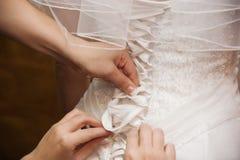 Händer som snör åt brudklänningen Arkivbild