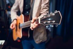 Händer som spelar den akustiska gitarren Royaltyfria Bilder