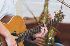 Händer som spelar den akustiska gitarren, slut upp royaltyfria foton