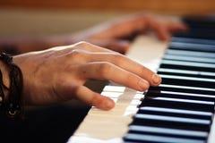 Händer som spelar en melodi på ett tangentbordmusikinstrument arkivfoto
