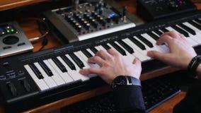 Händer som spelar midi det elektroniska pianot, medan komponera pop, vaggar hitlåt i hem- anteckna musikstudio med det blandande  arkivfilmer