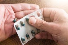 Händer som tar bort preventivpillerar från blåsapacke royaltyfria foton