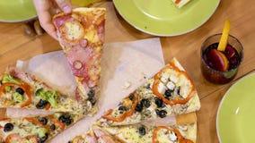 Händer som tar upp pizzaskivor på ett tabellslut arkivfilmer