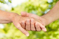 händer som tillsammans rymmer gamla människor Arkivbild