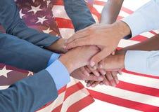 Händer som tillsammans sätts ovanför amerikanska flaggan Arkivbild