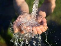 händer som tvättar sig, vatten som häller från ett klapp royaltyfri fotografi