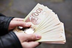 Händer som utanför rymmer kanadensaren hundra dollarräkningar Arkivbilder