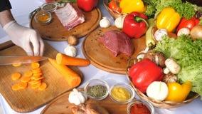 Händer som vänder morötter, klippte in i ett träbräde, mot bakgrunden av höna, nötkött, udde, grönsaker 1 livstid fortfarande sid arkivfilmer