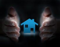 Händer täcker ett hus Arkivbild