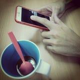 Händer trycker på till smartphoneskärmen med koppen kaffe i tappningfärgsignal Arkivbilder