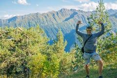 händer upp En turist i kortslutningar och en tröja som överst står av en klippa på bakgrunden av träd och att hålla ögonen på Royaltyfria Bilder