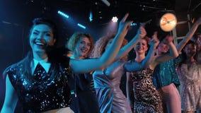 Händer upp - folkmassaflickor som festar och att dansa ultrarapid på en nattklubb stock video