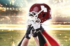Händerna av amerikanska fotbollsspelare med hjälmen på vit bakgrund Arkivfoton
