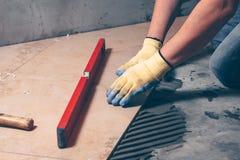 Händerna av arbetaren i handskar trycker på tegelplattan till golvet fotografering för bildbyråer