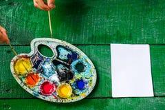 Händerna av barn med buntar Målarfärg på vattnet Färgpalett och rent ark Arkivbild