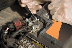 Händerna av bilmekanikern i disponibla handskar skruva av batterikopplingen Arkivfoto