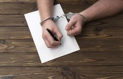 Händerna av brottslingen i handbojor skriver med en penna på papper arkivfoto