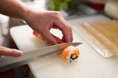 Händerna av den japanska `en s för sushisashimikocken baktalar arkivbild