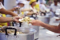 Händerna av det rikt ger mat till händerna av det fattigt Begrepp: Begreppet av att dela royaltyfri bild