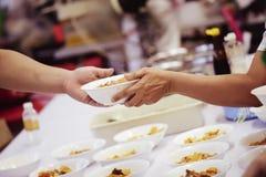 Händerna av det rikt ger mat till händerna av det fattigt Begrepp: Begreppet av att dela arkivbilder