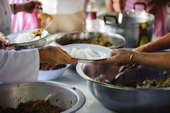 Händerna av det rikt ger mat till det fattigt och hungrigt royaltyfria foton