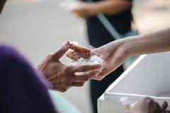 Händerna av det rikt ger mat till det fattigt och hungrigt arkivbild