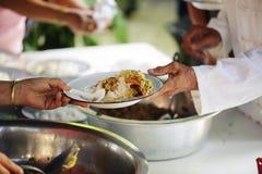 Händerna av det rikt ger mat till det fattigt och hungrigt arkivfoton