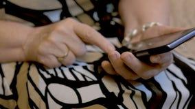 Händerna av en äldre kvinna som ringer sms på en smartphone Närbild lager videofilmer