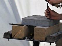 Händerna av en arbetarstenhuggare med stämjärnet på arbete, stenar tjock skiva på träkvarter för att bearbeta arkivbilder