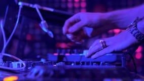 Händerna av en discjockey som utför i en nattklubb på ett parti Diskoljus arkivfilmer