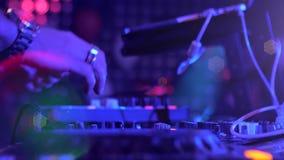 Händerna av en discjockey som utför i en nattklubb på ett parti Diskoljus stock video