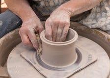 Händerna av en keramiker som formar leran på ett kasta hjul Arkivfoto