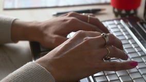 H?nderna av en kvinna som skriver en dator p? en st?ngd niv? lager videofilmer
