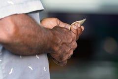 Händerna av en man som rymmer pengarrufiyaa, når att ha handlat, utomhus arkivbilder