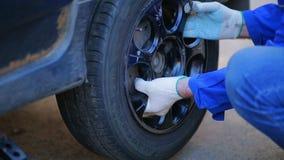 Händerna av en manlig mekaniker sätter ett gummihjul på axeln av bilen och drar åt muttrarna arkivfilmer