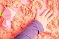 Händerna av ett barn som spelar med kinetisk sand arkivbilder