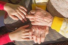 Händerna av farmodern och barnbarnet Royaltyfria Foton