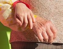 Händerna av farmodern och barnbarnet Arkivbilder