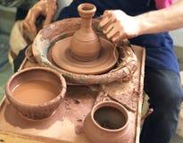 Händerna av keramikern som gör disken från brun lera arkivbilder