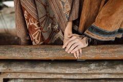 Händerna av män och kvinnor En man i en poncho poncho Royaltyfria Foton