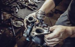 Händerna av mekaniker rymmer turbinen av en bilmotor arkivfoto