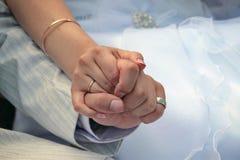 Händerna av nygifta personerna Arkivfoto