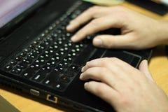 Händerna av programmeraren, honom som arbetar på en bärbar dator royaltyfria bilder